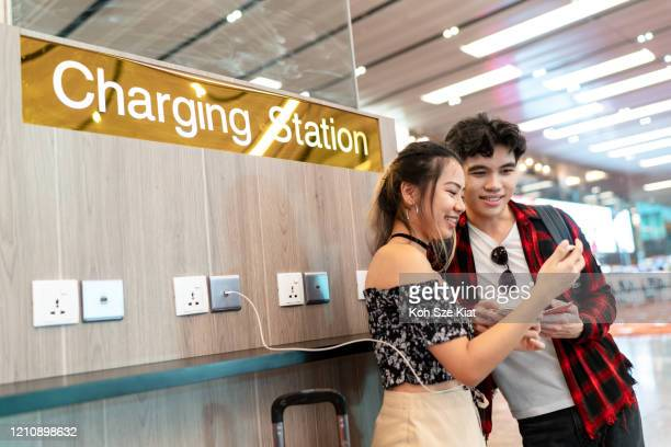 young asian couple enjoying free phone charge sharing at the airport - electric vehicle charging station stock pictures, royalty-free photos & images