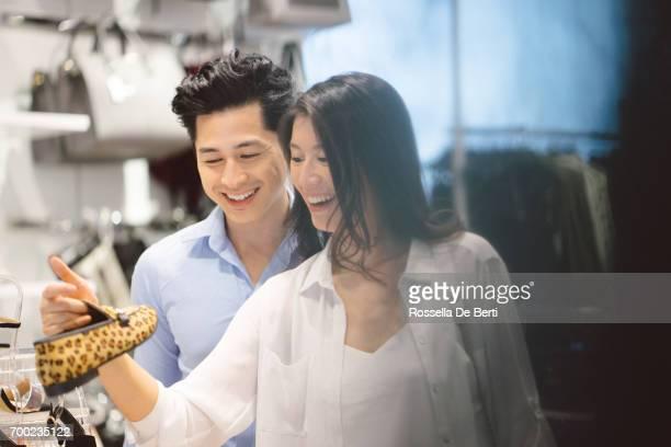 Young asian couple enjoying shopping in the mall