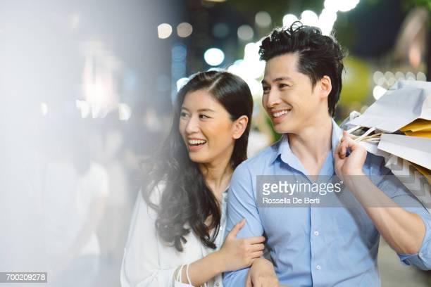 若いアジアのカップル ナイト マーケットで買い物を楽しんで