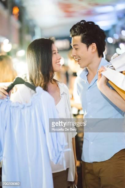 Young asian couple enjoying shopping in the night market