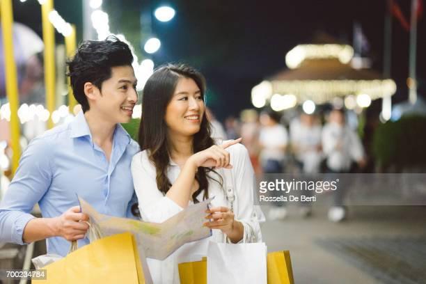 Jeune couple asiatique, bénéficiant d'achats sur le marché de nuit
