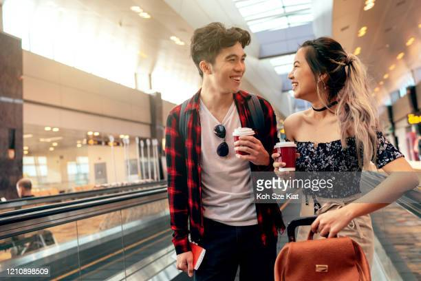 young asian couple going to their departure gate at the airport - travolator stock pictures, royalty-free photos & images