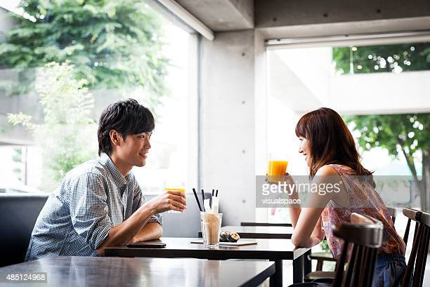 young asian couple having lunch in a cafe - east asia stock pictures, royalty-free photos & images