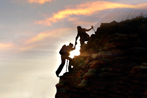 Young Asian couple  hikers climbing up  mountain cliff . Climbing ,Helps and Team work concept . - gettyimageskorea