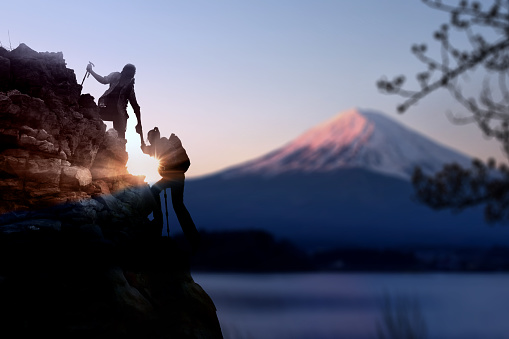 Young Asian couple  hikers climbing up on the peak of mountain near mountain Fuji .Climbing ,Helps and Team work concept . - gettyimageskorea