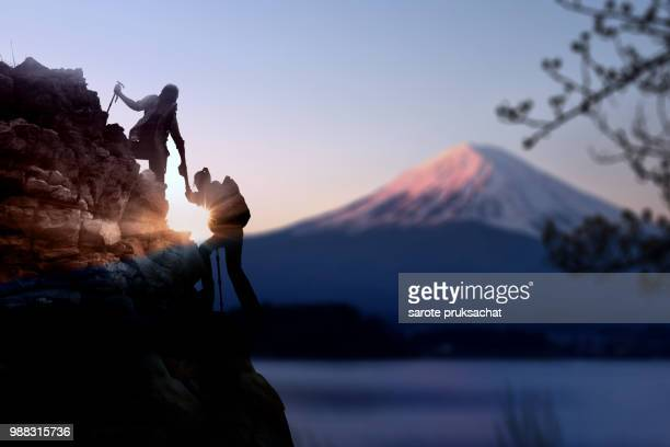 young asian couple  hikers climbing up on the peak of mountain near mountain fuji .climbing ,helps and team work concept . - outdoor pursuit stock pictures, royalty-free photos & images