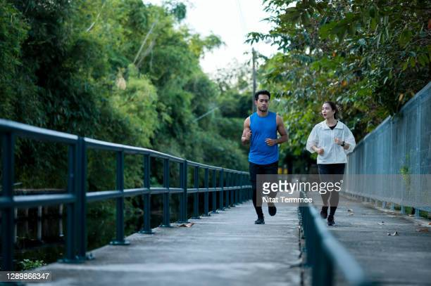 young asian couple morning jogging urban park outdoors. healthy, active lifestyle concepts. - coat stock pictures, royalty-free photos & images