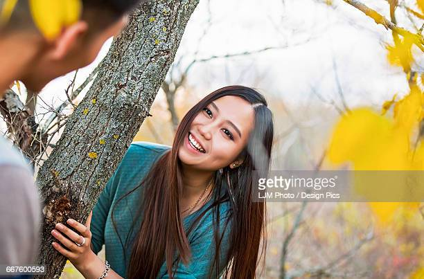 A young Asian couple on a romantic date outdoors and playing hide and seek in a park during autumn