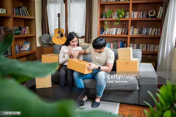 young asian couple opening a parcel together while sitting on a sofa in their living room. online shopping, stay at home. - unboxing stock pictures, royalty-free photos & images