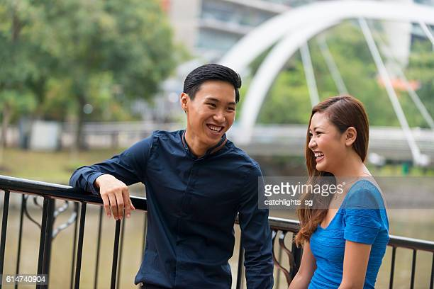 Young Asian Couple Scrolling in City Park
