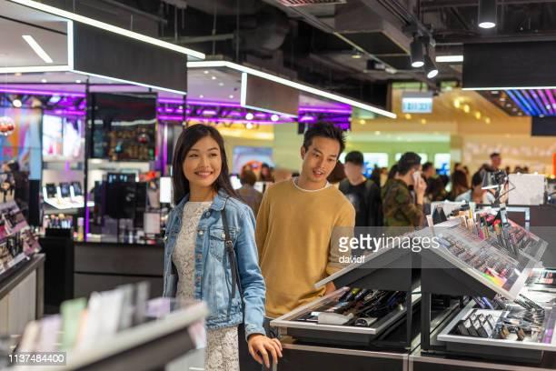 化粧品売り場での若いアジアのカップルのショッピング - 百貨店 ストックフォトと画像