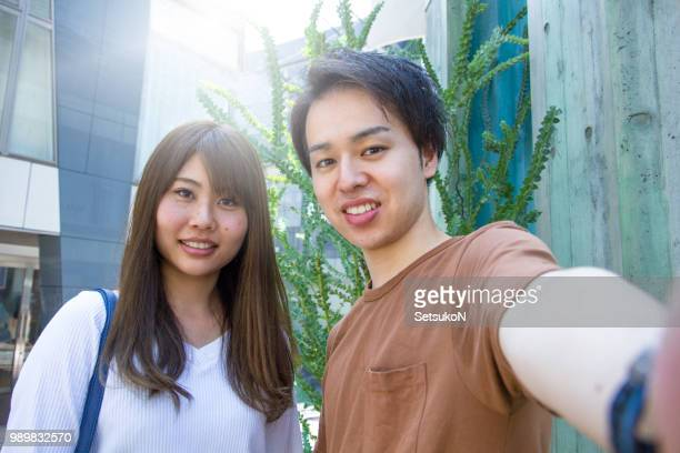 young asian couple taking selfie outside. - self portrait photography stock pictures, royalty-free photos & images