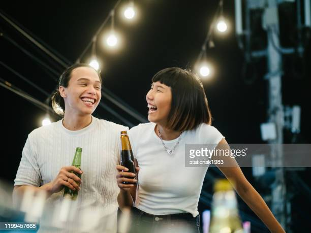 young asian couple toasting with beer at rooftop party - girlfriend stock pictures, royalty-free photos & images