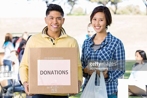 Young Asian couple volunteering at outdoor food donation drive