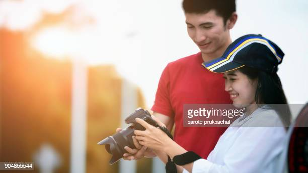 Young Asian couple watching photo and sunset background .