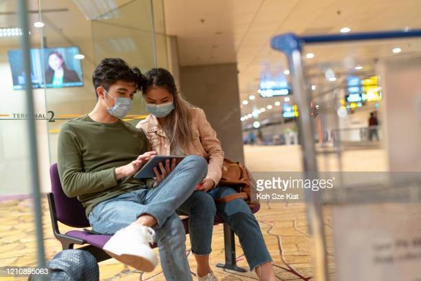 young asian couple with surgical mask in the airport - singapore stock pictures, royalty-free photos & images