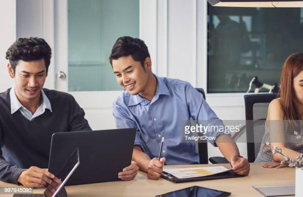Junge asiatische Mitarbeiter in fröhlicher Stimmung, Business-meeting mit Team Diskussion Brainstorming, Start Projektpräsentation oder Teamwork Konzept im Büro