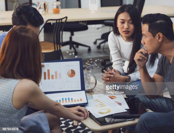 young asian coworkers in serious business meeting with team discussion brainstorming, startup project presentation or teamwork concept, at office - stock trader stock pictures, royalty-free photos & images