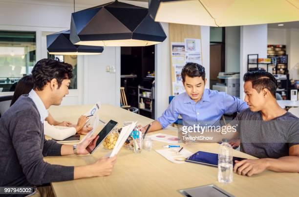 Junge asiatische Mitarbeiter in ernsthafte Business-Meeting mit Team Diskussion Brainstorming, Start Projektpräsentation oder Teamwork Konzept, im Büro