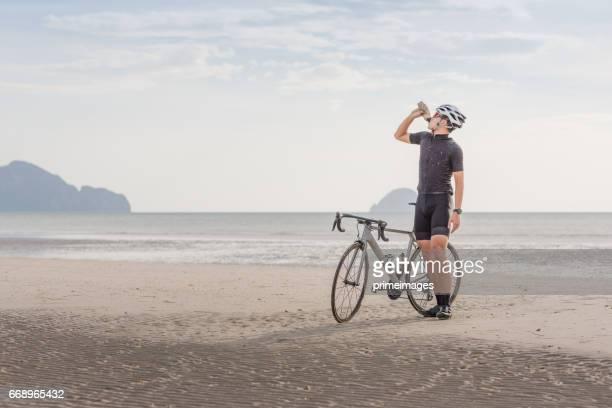 bicicleta de paseo de hombre joven ciclista asia la playa de la puesta del sol - human powered vehicle fotografías e imágenes de stock