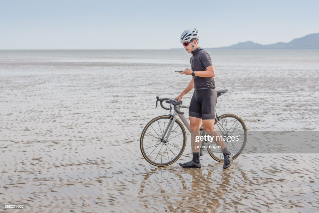 Young asian cyclist man ride  bicycle  the beach at the sunset : Stock Photo