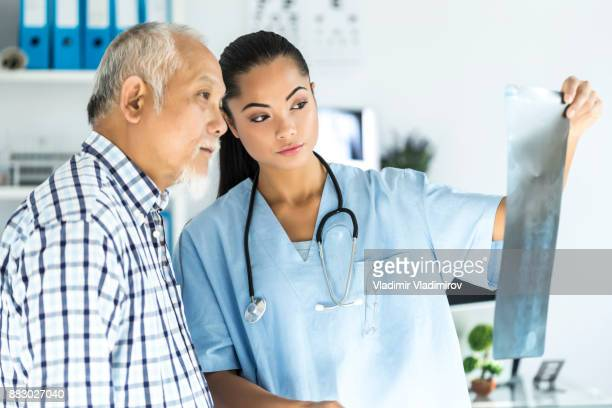 young asian doctor talking to a patient in her cabin - medical x ray stock pictures, royalty-free photos & images