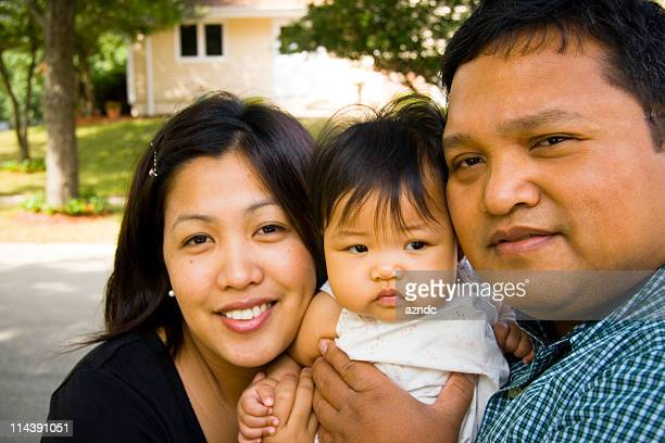 Young Asian family smiling, standing in neighborhood