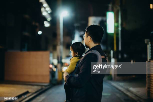 young asian father carrying cute little daughter exploring while walking through city street at night - 片親 ストックフォトと画像