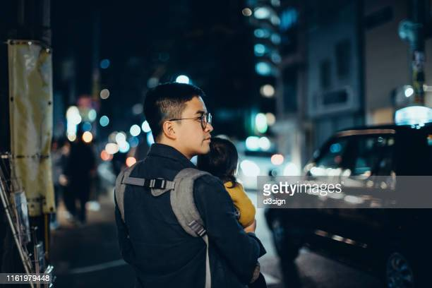 young asian father carrying cute little daughter walking through city street at night, against illuminated cityscape with busy traffic - carrying stock pictures, royalty-free photos & images