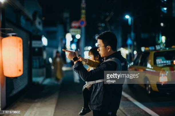 young asian father carrying cute little daughter walking through city street at night, pointing and looking at a store window - 仕事後 ストックフォトと画像