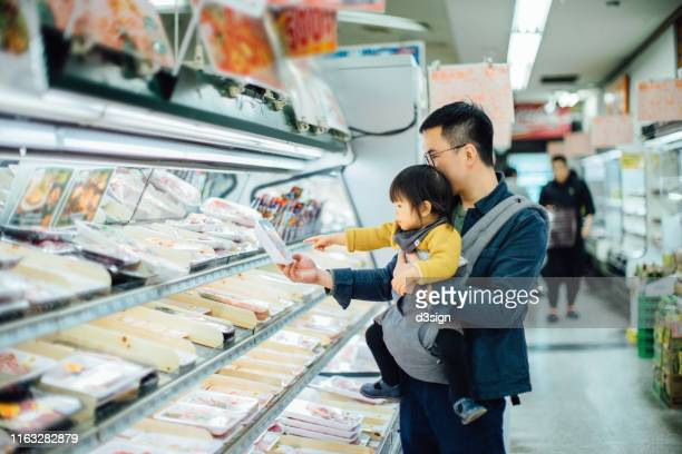 young asian father grocery shopping with cute little daughter in supermarket, they are shopping for fresh poultry - 主夫 ストックフォトと画像