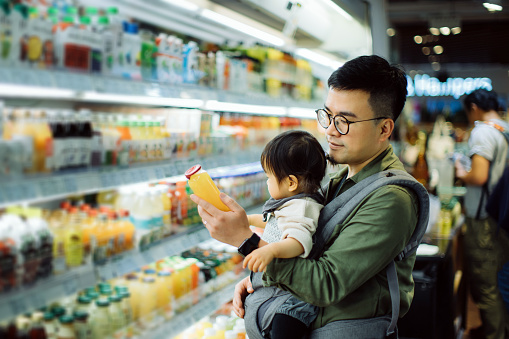 Young Asian father with cute little daughter grocery shopping for fresh fruit juice in supermarket - gettyimageskorea
