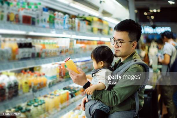young asian father with cute little daughter grocery shopping for fresh fruit juice in supermarket - convenience store stock pictures, royalty-free photos & images