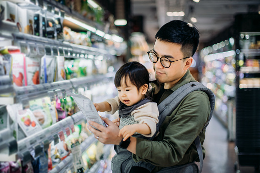 Young Asian father with cute little daughter grocery shopping for organic products in supermarket - gettyimageskorea