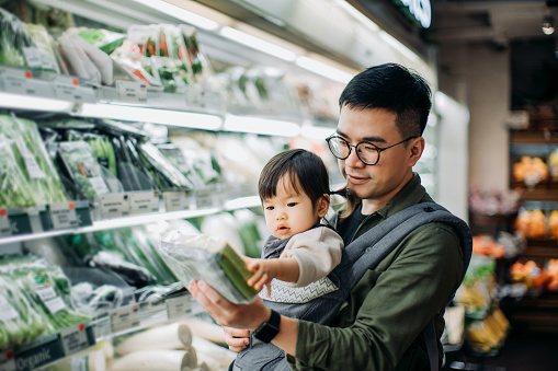 Young Asian father with cute little daughter grocery shopping for fresh organic vegetables in supermarket - gettyimageskorea