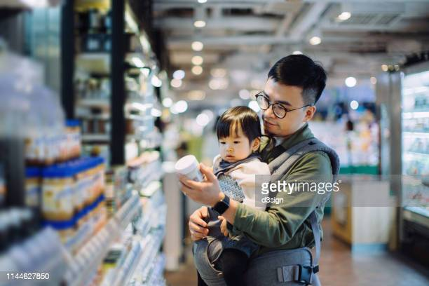 young asian father with cute little daughter grocery shopping for daily necessities in supermarket - 主夫 ストックフォトと画像