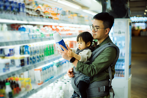 Young Asian father with cute little daughter grocery shopping for dairy products in supermarket - gettyimageskorea