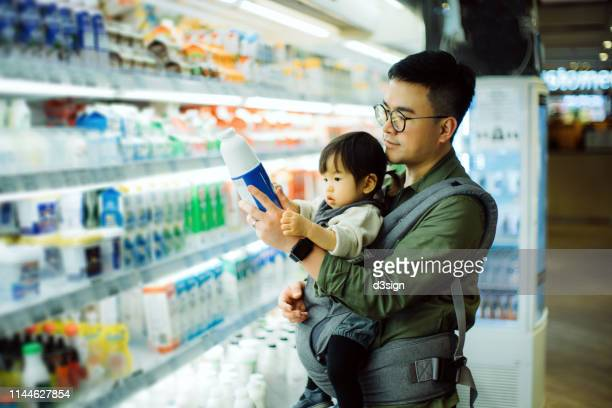 Young Asian father with cute little daughter grocery shopping for dairy products in supermarket