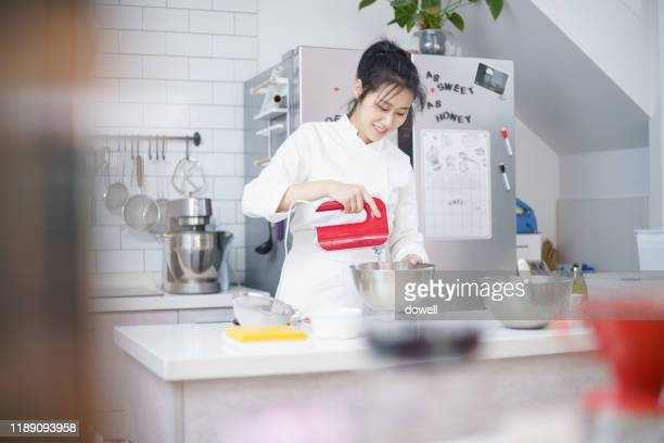 young asian female mix the cake dough in the bowl with a blender - female whipping stock-fotos und bilder