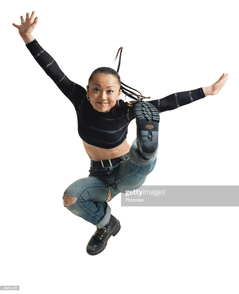 young asian female ripped jeans and blue shirt braid hair jumps into the air and flairs arms smiling : Foto de stock