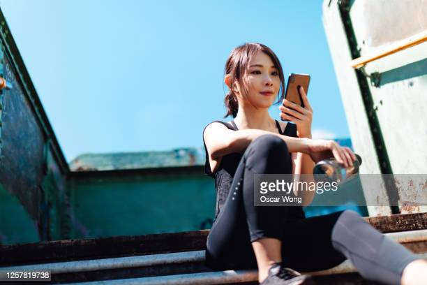 young asian female runner using smartphone while sitting on staircase to take a break in art district, city downtown - art stock pictures, royalty-free photos & images