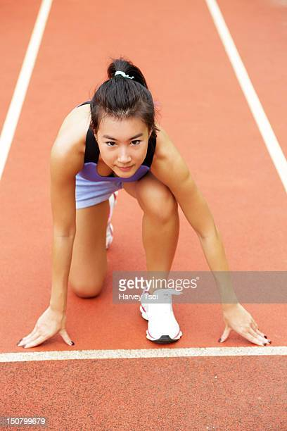 Young Asian female track runner preparing to race