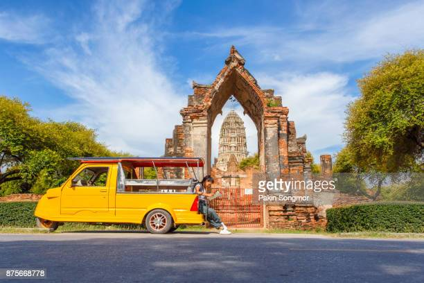 young asian female traveler with backpack traveling sitting on taxi or tuk tuk and see map travel with old temple (wat mahathat) background, ayutthaya province, thailand - provincia di chiang mai foto e immagini stock