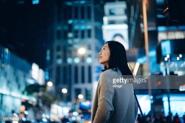 young asian female traveller enjoying holiday, exploring and strolling in downtown city street at night - independence stock pictures, royalty-free photos & images
