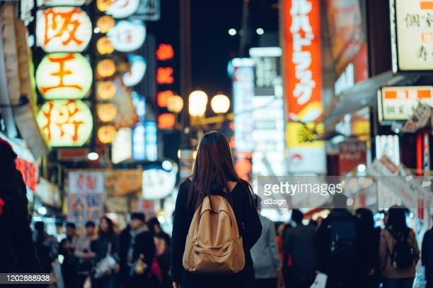 young asian female traveller exploring and strolling along the busy and colourful neon signboard downtown city street at night in osaka, japan - japan stock pictures, royalty-free photos & images