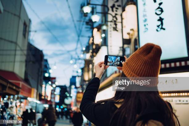 young asian female traveller photographing the vitality of local city street scene with smartphone while travelling in kyoto, japan - carefree stock pictures, royalty-free photos & images