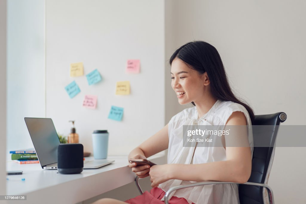 Young asian female working from home with smart assistant speaker : Stock Photo