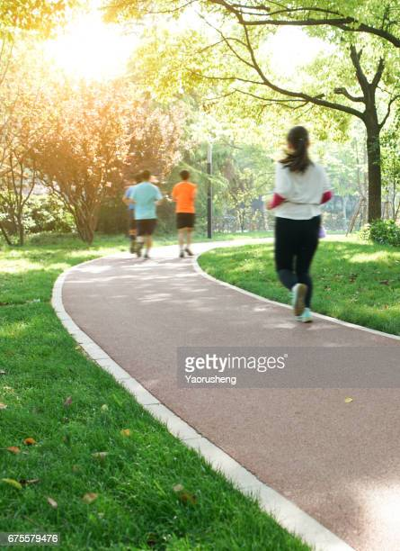Young asian fitness runner running on forest track