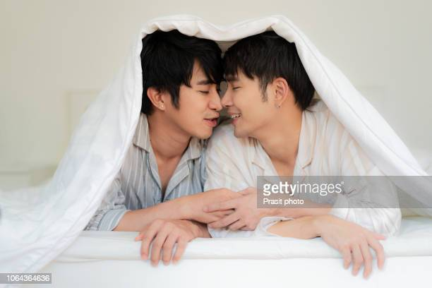 young asian gay couple lying under blanket on bed in light room. - sex stock photos and pictures
