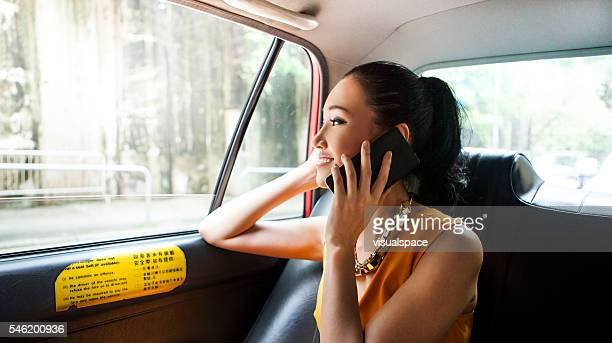 Young Asian Girl Calling With Her Friend While On Taxi